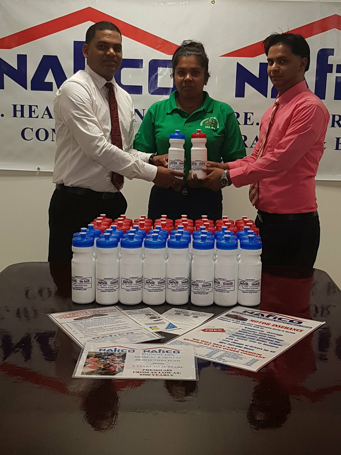 In picture, NALICO/NAFICO representatives, Mr. Anil Singh, Fire Manager and Mr. Hemendra Persaud, Internal Auditor hands over water bottles to Ms. Praneva Singh, a Graduate Senior Mistress at Annandale Primary School and a member of the STEAM FAIR team.