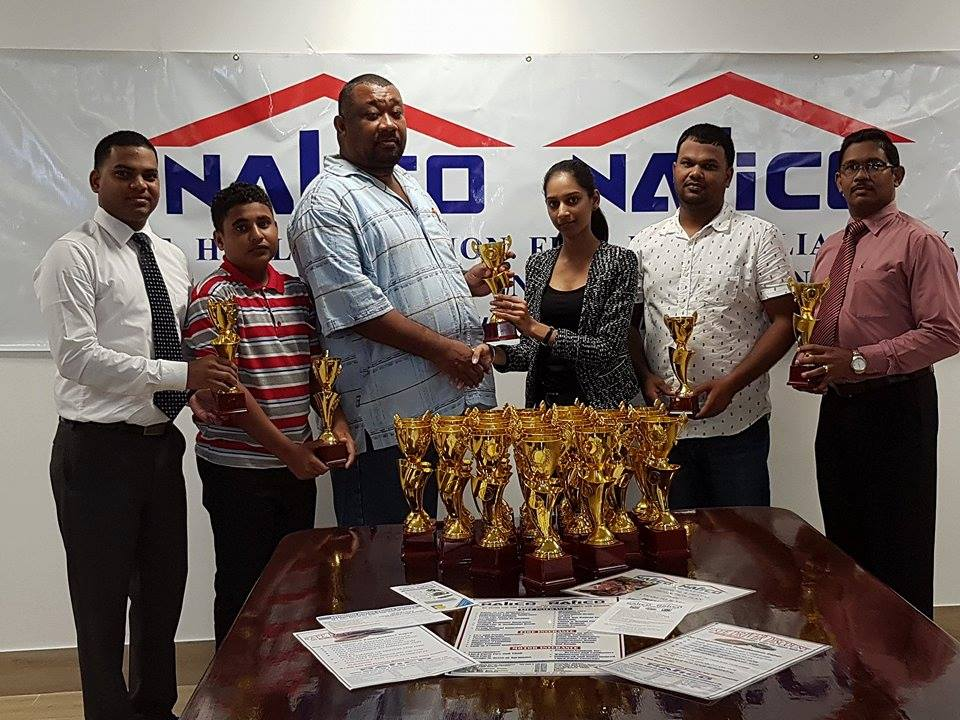 """Nalico/Nafico donates trophies to the Rose Hall Town Youth & Sports Club for their 28th annual """"Say No, Say Yes"""" program. In picture, representatives of Nalico/Nafico, Ms. Sonia Charran (Marketing Coordinator), Mr. Anil Singh, Fire Insurance Manager, (far left), Mr. Shivraj Singh, Life Insurance Manager (far right) hands over the trophies to representatives from the Rose Hall Town Youth & Sports Club, Mr. Foster, Secretary, Mr. Mark Papannah, Vice President and Mr. Simon Naidu, Assistant Secretary."""